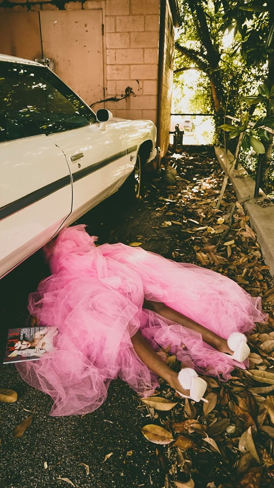 brown legs draped in a pink tulle gown hang out from under an old car.